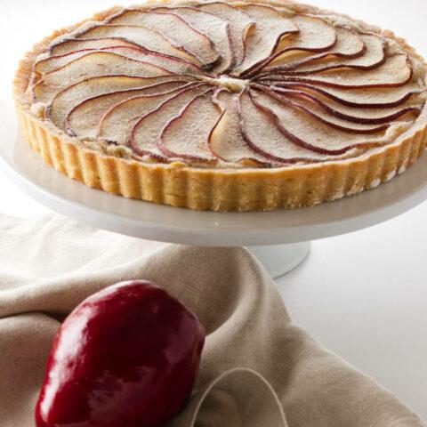A pear frangipane tart on a dessert platter.