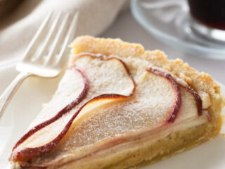 A slice of pear frangipane tart on a dessert plate.
