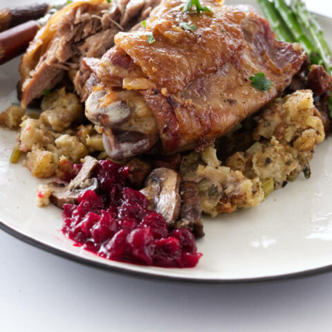 close up view of a serving of roasted turkey thigh with mushrooms stuffing