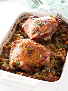 Casserole dish with stuffing topped with two turkey thigs