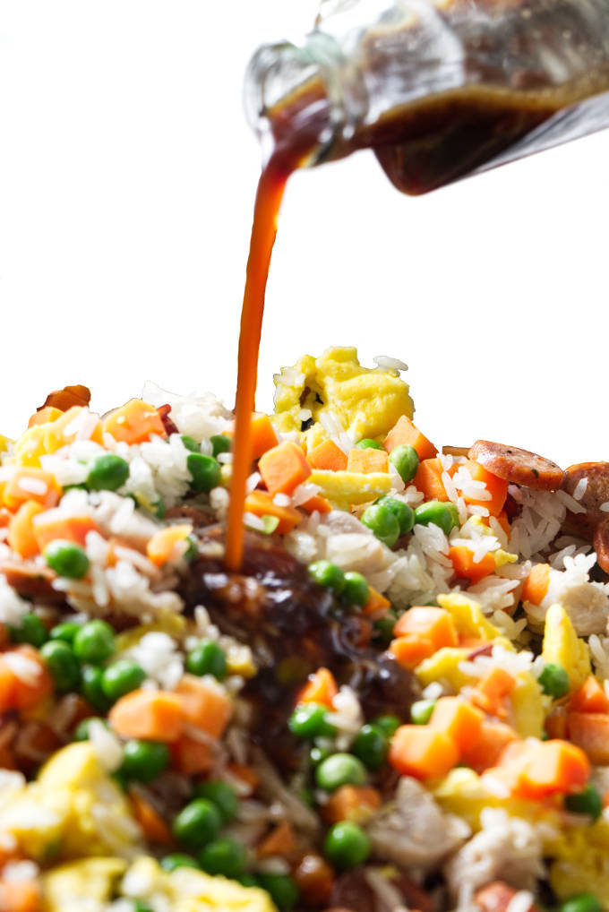 Fried rice sauce being poured over fried rice.